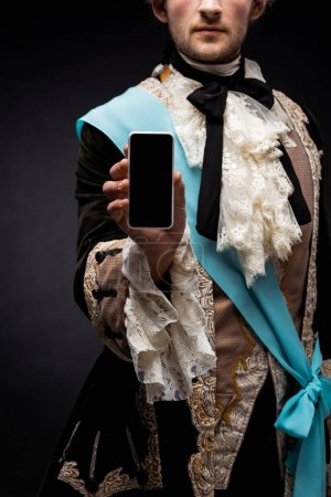 Photo for Cropped view of victorian man holding smartphone with blank screen on black - Royalty Free Image