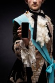 "Постер, картина, фотообои ""cropped view of victorian man holding smartphone with blank screen on black """