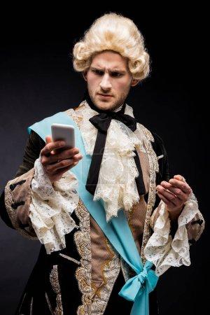 Photo pour Beau homme victorien retenant le smartphone sur le noir - image libre de droit