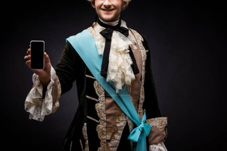 Photo for Cropped view of happy victorian man holding smartphone with blank screen on black - Royalty Free Image