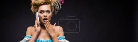 Photo pour Tir panoramique de la femme victorienne surprise parlant sur le smartphone sur le noir - image libre de droit