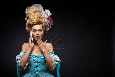 Photo for Surprised young victorian woman talking on smartphone on black - Royalty Free Image