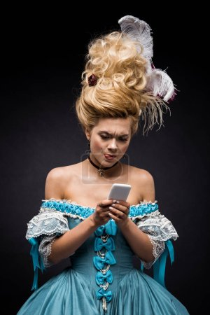 Photo for Attractive young victorian woman in blue dress using smartphone while showing tongue on black - Royalty Free Image