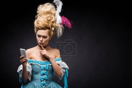 Photo pour Jeune femme victorienne dans la robe bleue regardant le smartphone et affichant le signe de silence sur le noir - image libre de droit