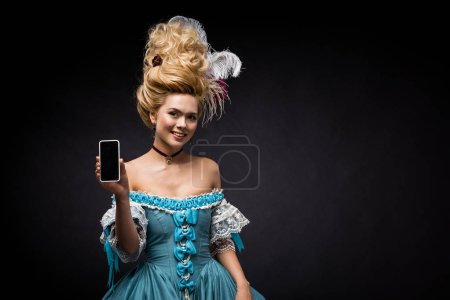 Photo for Young victorian woman in blue dress holding smartphone with blank screen on black - Royalty Free Image