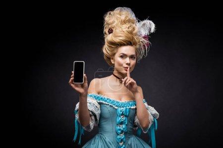 Photo pour Jeune femme victorienne en robe bleue tenant smartphone avec écran blanc et montrant signe de silence sur noir - image libre de droit