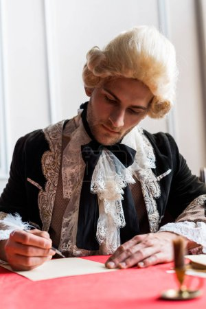 Foto de Selective focus of handsome victorian man in wig writing letter - Imagen libre de derechos