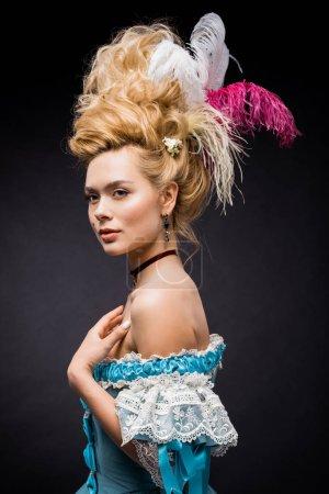 Photo pour Femme victorienne élégante et attrayante avec des plumes dans la perruque sur le noir - image libre de droit