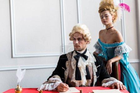 Photo pour Femme victorienne attirante restant près de l'homme pompeux retenant la plume près du papier - image libre de droit