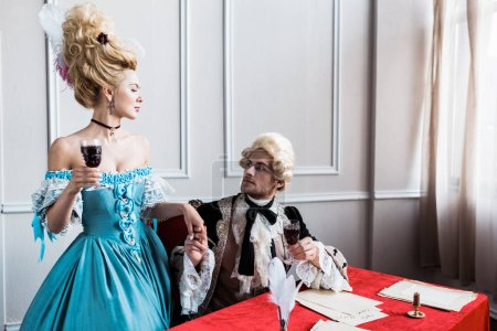 victorian girl in wig holding hands with handsome pompous man with glass wine sitting near papers
