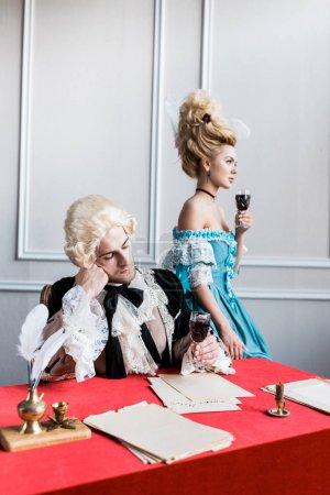 Foto de Triste hombre victoriano en peluca sosteniendo vino de vidrio cerca de mujer pomposa - Imagen libre de derechos