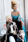 """Постер, картина, фотообои """"викторианская женщина, стоящая рядом с мужчиной в парике, сидя на антикварном стуле"""""""