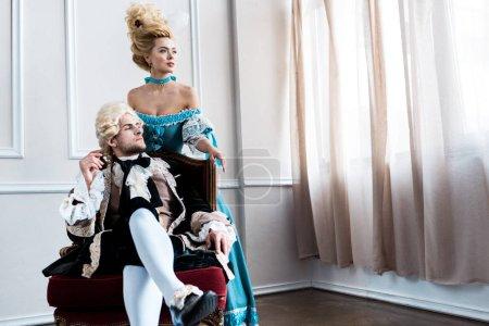 Photo pour Femme victorienne restant près de l'homme beau dans la perruque s'asseyant sur la présidence antique - image libre de droit