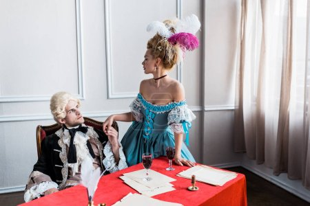 Photo pour Bel homme victorien dans la perruque retenant des mains avec la femme pompeuse près des glaces de vin - image libre de droit
