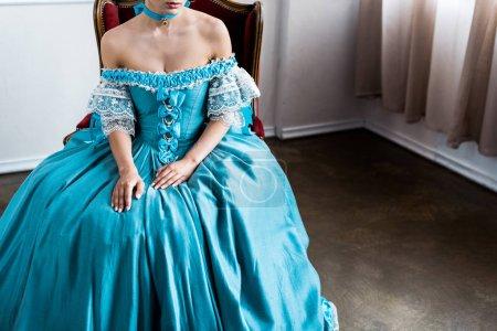 Foto de Vista recortada de la mujer victoriana sentada en silla antigua - Imagen libre de derechos