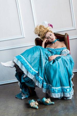 Photo pour Femme victorienne ennuyée en perruque avec des plumes assis sur une chaise antique - image libre de droit