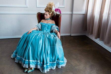 Photo pour Femme victorienne pompeuse dans la robe bleue s'asseyant sur la présidence antique - image libre de droit