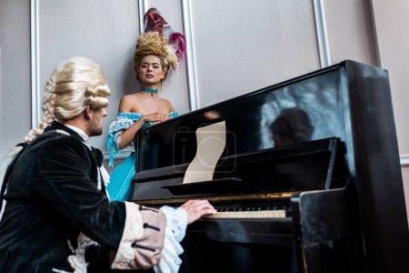 Photo pour Foyer sélectif de la femme victorienne regardant l'homme dans la perruque jouant le piano - image libre de droit