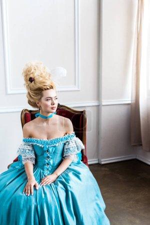 Photo pour Belle femme victorienne dans la robe bleue s'asseyant sur la présidence antique - image libre de droit