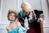"""Постер, картина, фотообои """"низкий угол зрения викторианской человек смотрит на привлекательную женщину в парике, сидя на антикварном стуле"""""""