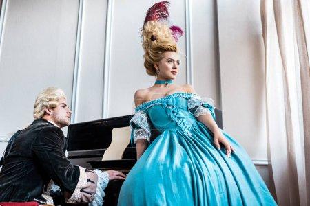 Photo pour Attrayant victorienne femme en robe bleue debout près de l'homme en perruque jouer du piano - image libre de droit