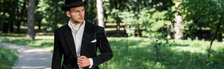 Photo for Panoramic shot of handsome victorian man in hat standing outside - Royalty Free Image