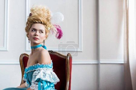Photo pour Belle femme victorienne dans la perruque avec des plumes s'asseyant sur la présidence antique - image libre de droit