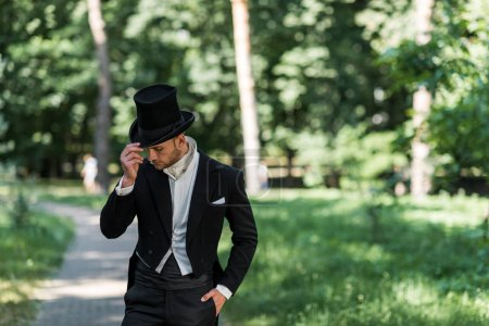 Photo for Handsome young victorian man touching hat and standing with hand in pocket outside - Royalty Free Image