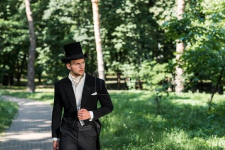 handsome young victorian man in hat standing outside