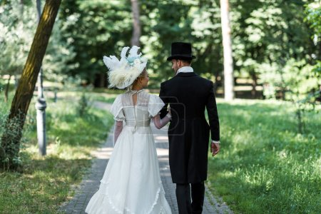Photo for Victorian man and woman in hats walking outside near green trees - Royalty Free Image