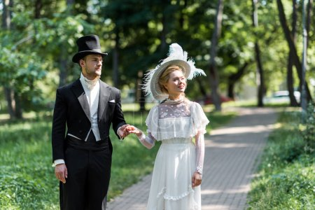 victorian man and woman in hats holding hands while standing outside near green trees