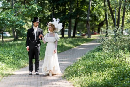 Photo for Handsome victorian man and attractive woman in hats holding hands while walking outside - Royalty Free Image