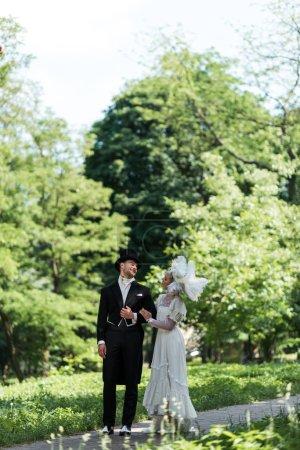 Photo pour Bel homme victorien regardant la femme dans le chapeau tout en marchant à l'extérieur - image libre de droit