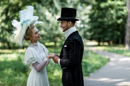 happy young victorian woman and handsome man in hat holding hands outside
