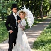 """Постер, картина, фотообои """"красивый викторианский мужчина, стоящий с рукой в кармане рядом с женщиной, держащей зонтик"""""""