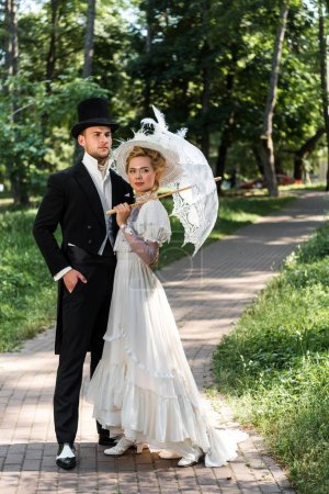 handsome victorian man standing with hand in pocket near woman holding umbrella