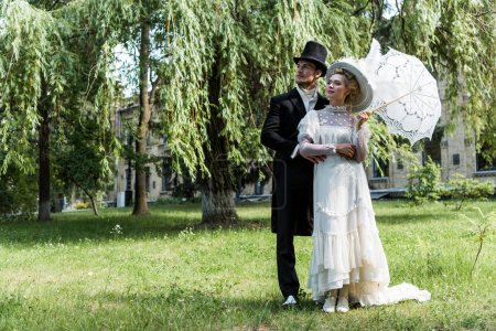 handsome victorian man standing with woman holding umbrella