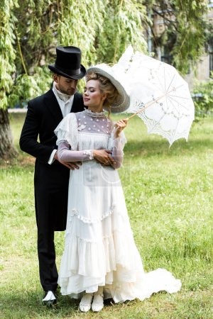 handsome victorian man standing with attractive woman holding umbrella