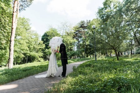 Photo for Victorian man and woman covering faces while holding umbrella - Royalty Free Image
