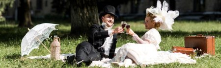 Photo for Panoramic shot of happy man and woman siting on blanket and clinking wine glasses - Royalty Free Image