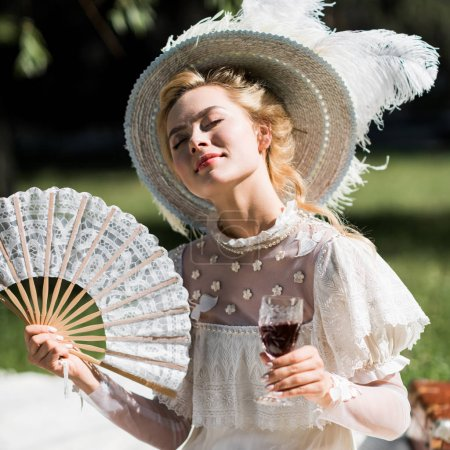 Photo for Cheerful young victorian woman holding fan and wine glass - Royalty Free Image