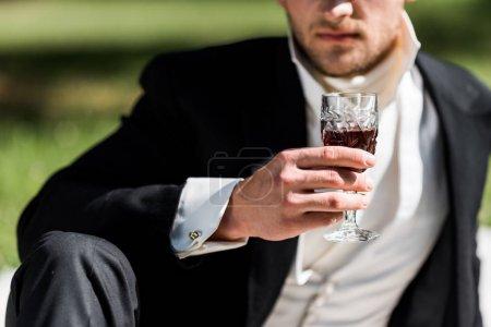 Foto de Vista recortada del hombre victoriano sosteniendo copa de vino con bebida - Imagen libre de derechos