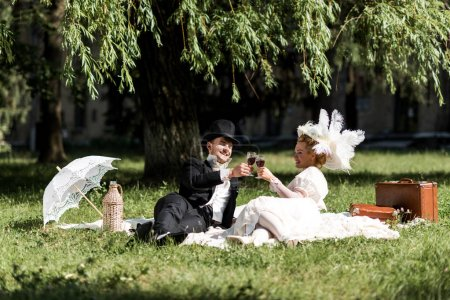 Photo for Happy man and woman siting on blanket and clinking wine glasses - Royalty Free Image