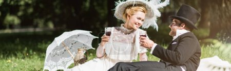 Photo for Panoramic shot of happy man and woman holding wine glasses - Royalty Free Image