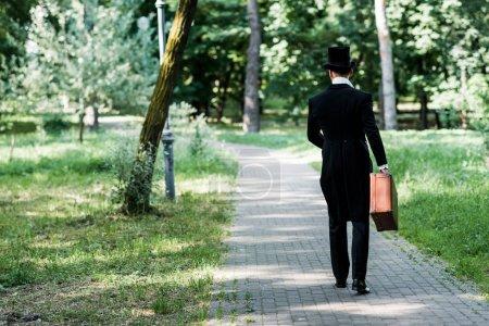 Photo pour Vue arrière de l'homme victorien dans le bagage de fixation de chapeau et marchant à l'extérieur - image libre de droit