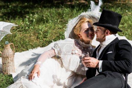 Photo pour Femme victorienne heureuse s'asseyant sur la couverture et regardant l'homme dans le verre de vin de fixation de chapeau - image libre de droit