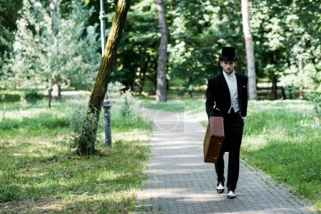 Photo for Handsome victorian man in hat holding baggage and walking outside - Royalty Free Image