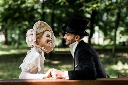 Photo for Handsome aristocratic man holding hands with cheerful victorian woman in hat - Royalty Free Image