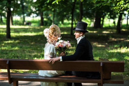 Photo for Handsome aristocratic man sitting with cheerful victorian woman in hat on bench - Royalty Free Image