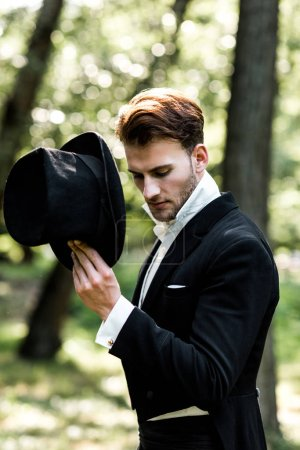 Photo for Handsome aristocratic man holding hat while standing in suit - Royalty Free Image